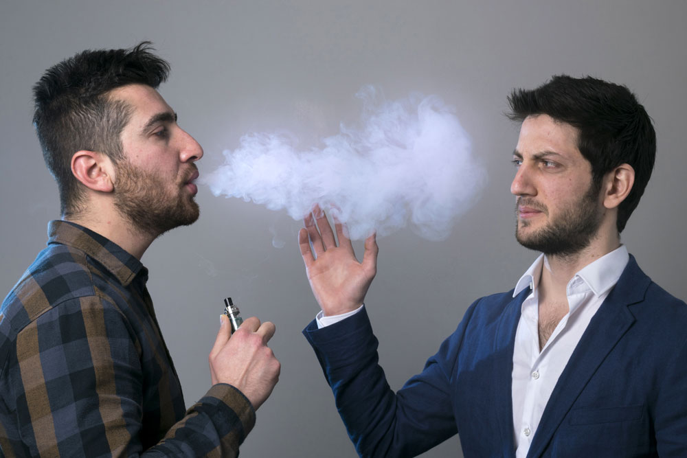 man blowing vapour into the face of another man